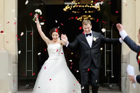 familia en la iglesia: Apenas pares casados ??bajo una lluvia de pétalos de rosa Foto de archivo