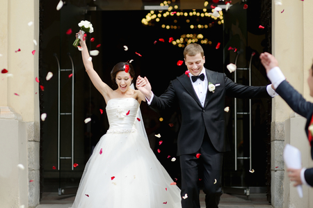 people laughing: Just married couple under a rain of rose petals