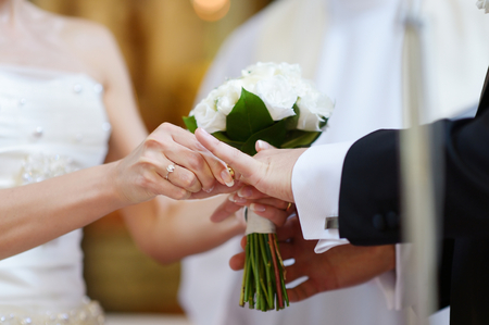 Bride putting a ring on grooms finger during wedding ceremony Banco de Imagens