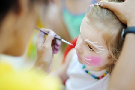 face: Adorable little girl getting her face painted