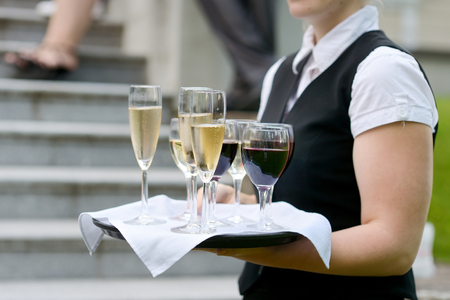 skoal: Waitress with dish of champagne and wine glasses Stock Photo