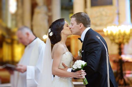 pareja de esposos: Novia y novio que se besan en una iglesia después de la ceremonia de la boda Foto de archivo