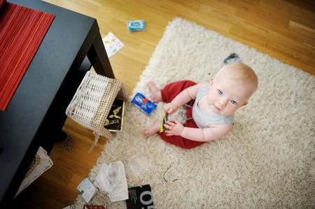 desorden: Bebé adorable que hace un lío en casa Foto de archivo