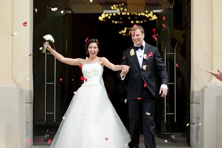 pareja de esposos: Apenas pares casados ??bajo una lluvia de pétalos de rosa Foto de archivo