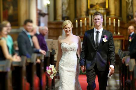 La novia y el novio salir de la iglesia después de una ceremonia de la boda