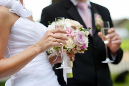 Bruden håller en brudbukett och ett glas champagne