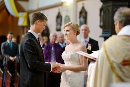 feier: Braut und Bräutigam in der Kirche während einer Hochzeitszeremonie Lizenzfreie Bilder
