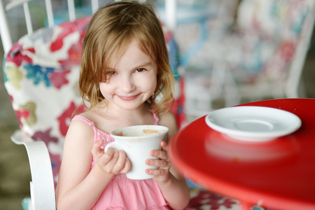 chocolate caliente: Adorable girl drinking hot chocolate in outdoor restaurant Foto de archivo