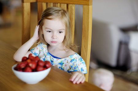 food allergy: Thoughtful girl sitting next to fresh strawberries in a bowl Stock Photo