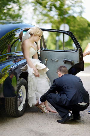 Groom helping his bride to put on her shoes photo