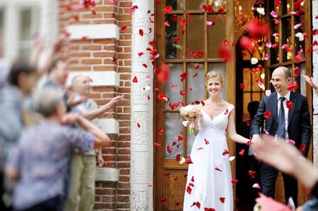 recien casados: Apenas pares casados ??bajo una lluvia de pétalos de rosa Foto de archivo