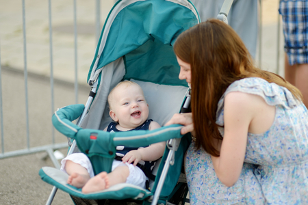 padres hablando con hijos: Joven madre hablando con sonriente bebé en un cochecito Foto de archivo