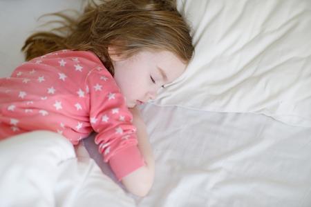 niño durmiendo: Adorable niña durmiendo en una cama
