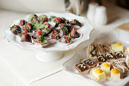 chocolate covered strawberries: A plate of chocolate covered strawberries and others sweets