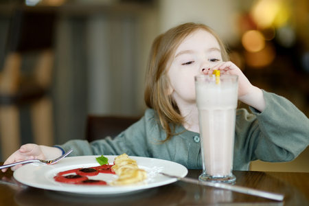 Cute little girl drinking milk coctail in a cafe Stock Photo