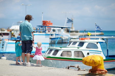 cos: Young father and his kids at fisherman village in Greece