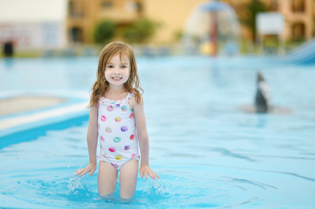 children swimsuit: Cute little girl having fun in a swimming pool