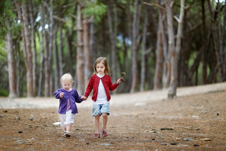 coexist: Two little sisters having a walk in the woods