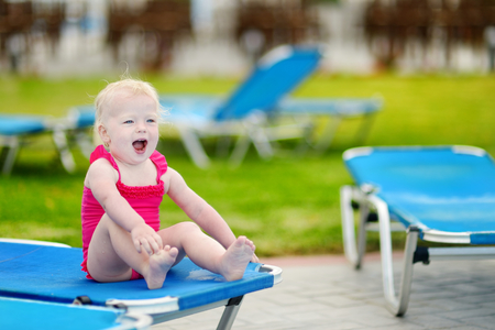Adorable toddler girl sitting on a sunbed by a swimming pool