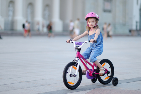pink bike: Little girl riding a bike in a city