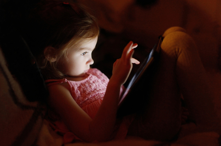 Adorable little girl playing on a digital tablet