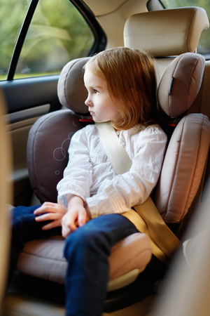 seat: Adorable little girl sitting safely in car seat