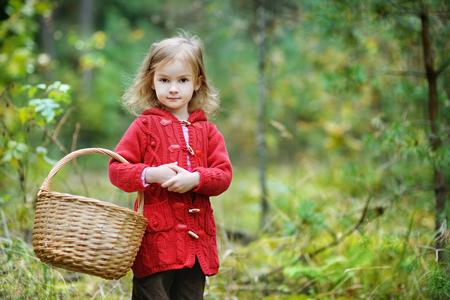 niño abrigado: Cosecha de la muchacha pequeños lindos setas en el bosque Foto de archivo