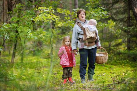 niño abrigado: Abuela y sus chicas recogiendo setas en el bosque Foto de archivo