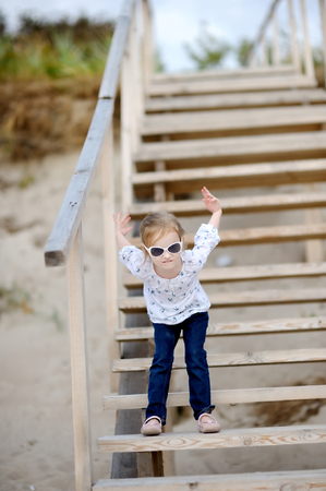Adorable girl standing on the stairs by the sea photo