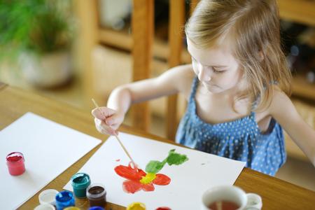 preschool classroom: Cute little girl is drawing with paints in preschool