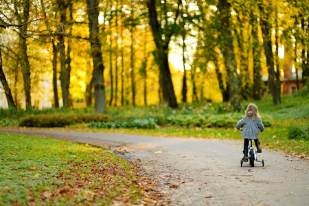 fashionable girl: Adorable girl riding a bike on beautiful autumn day