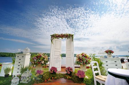 꽃으로 장식 된 결혼식 아치로 흰색 멋진 문