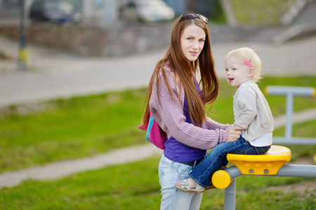 cradling: Young mother and her adorable toddler daughter
