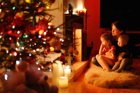 family indoors: Young mother and her daughters by a fireplace on Christmas