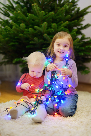 decorating christmas tree: Two little sisters decorating Christmas tree