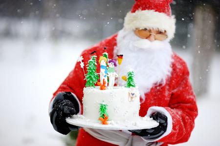 Traditionele Kerstman en een fancy verfraaide cake van Kerstmis