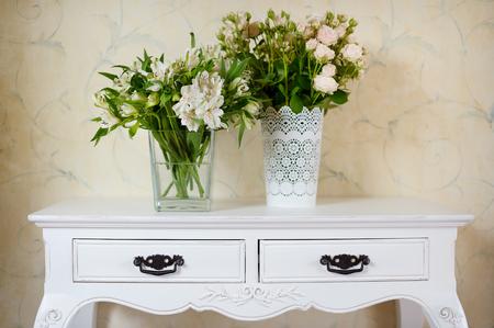 vase: White vase full of white flowers on a counter