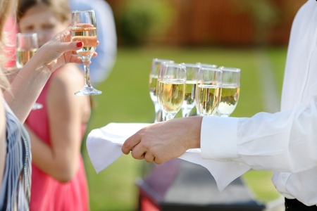 skoal: Waiter with dish of champagne and wine glasses