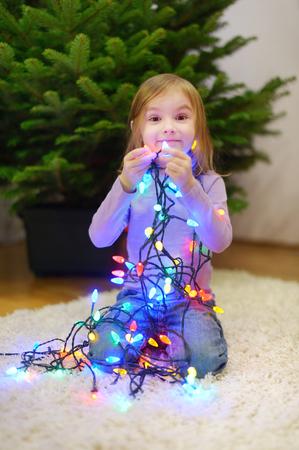 decorating christmas tree: Adorable little girl decorating Christmas tree