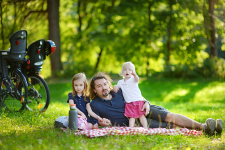 picnicking: Young father and his daughters picnicking in the park Stock Photo