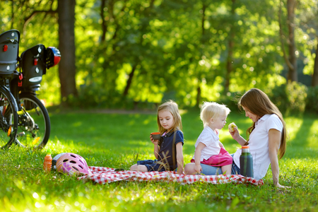 picnicking: Young mother and her daughters picnicking in the park Stock Photo