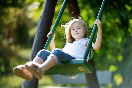playground ride: Adorable girl having fun on a swing on summer day Stock Photo