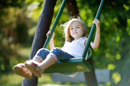 columpios: Niña adorable que se divierte en un columpio en día de verano