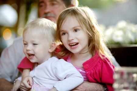 granddaughters: Grandfather hugging his two granddaughters