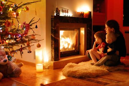 uvnitř: Mladá matka a její dcery u krbu na Vánoce Reklamní fotografie