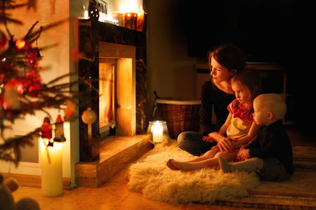 decorated christmas tree: Young mother and her daughters by a fireplace on Christmas
