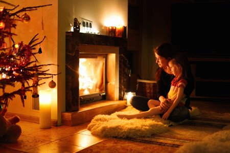 fireplace family: Young mother and her daughter by a fireplace on Christmas