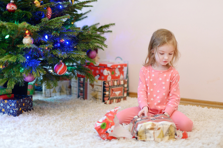 christmas morning: Young girl unwrapping presents on Christmas morning Stock Photo