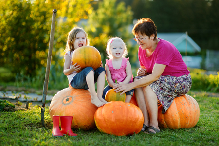 Two little sisters and their grandmom sitting on a huge pumpkins photo
