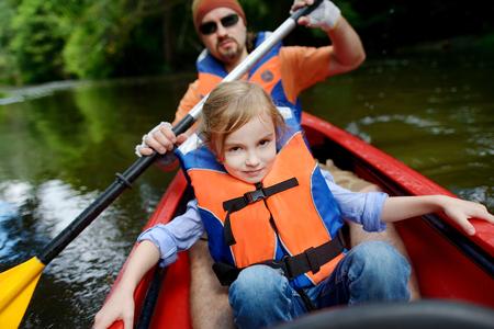 jezior: Mała dziewczynka i jej ojciec na kajaku na lato